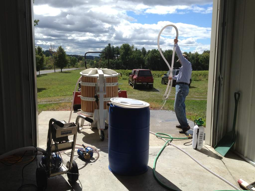 Gerry is cleaning hoses in the winery after pressing.